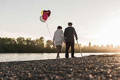 Back view of senior couple with balloons strolling at riverside in the evening - p300m1460512 by Uwe Umstätter