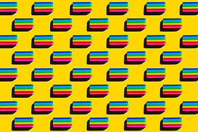 Pattern of rainbow colored erasers against yellow background - p300m2199079 by Xavier Lorenzo