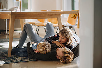 Happy relaxed family lying on the floor together at home - p300m2205533 by Kniel Synnatzschke