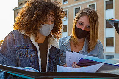 Female friends studying with protective mask while standing against education building in university campus - p300m2225892 by Ignacio Ferrándiz Roig