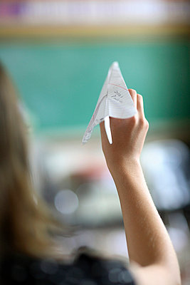 Teen girl holding paper airplane - p3721893 by James Godman