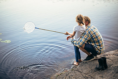 High angle view of father and daughter fishing in lake - p426m2213229 by Maskot