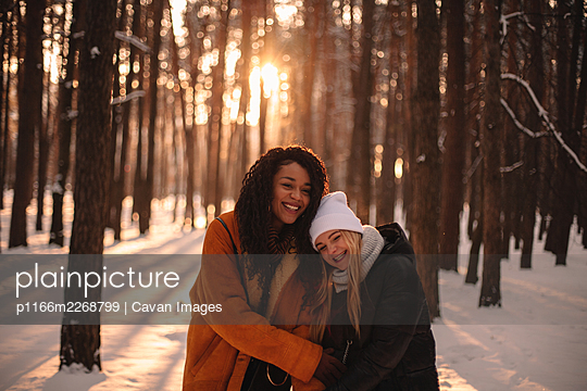 Portrait of happy girlfriends embracing while standing in snowy park - p1166m2268799 by Cavan Images