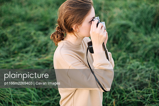 Pretty woman holding film camera in a field - p1166m2269403 by Cavan Images