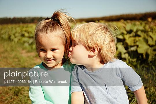Boy kissing girl on cheek - p1427m2283184 by Roberto Westbrook
