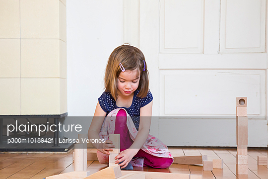 Little girl crouching on floor playing with wooden building bricks - p300m1018942f by Larissa Veronesi