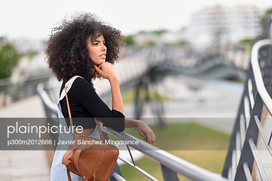 Young woman with brown leather backpack standing on a bridge looking at distance - p300m2012666 von Javier Sánchez Mingorance