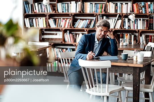Mature businessman working while using digital tablet sitting at table in cafe - p300m2293667 by Joseffson