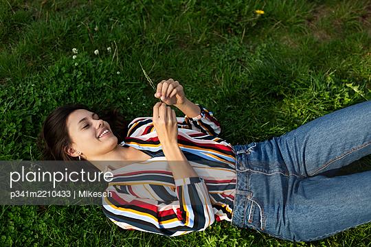 Junge Frau auf einer Wiese mit Grashalm - p341m2210433 von Mikesch