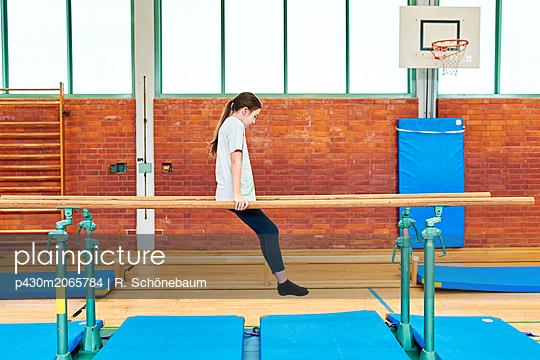 Mädchen turnt am Barren - p430m2065784 von R. Schönebaum