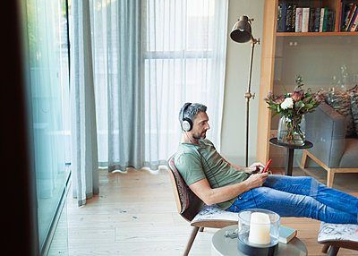 Man relaxing in living room, listening to music with mp3 player and headphones - p1023m2196665 by Paul Bradbury