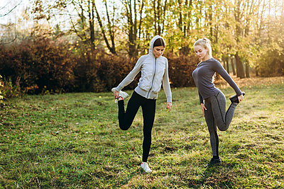 Morning fitness in the park. Two young girls are doing exercises. - p1166m2171848 by Cavan Images