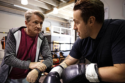 Trainer and male boxer talking in gym - p1192m2033903 by Hero Images