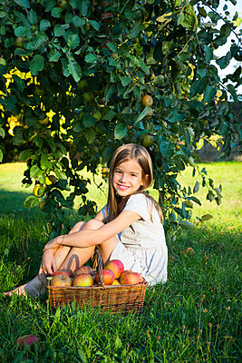 Portrait of happy little girl sitting on a meadow with wickerbasket of picked apples - p300m2070278 von Larissa Veronesi