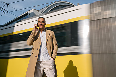 Portrait of businessman on the phone standing in front of driving tramway, Berlin, Germany - p300m2143412 von Hernandez and Sorokina