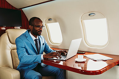 Young businessman concentrating while working on laptop in private jet - p300m2256385 by OneInchPunch