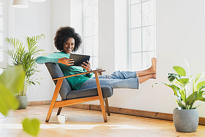 Smiling woman using digital tablet while sitting on armchair at home - p300m2276429 by Steve Brookland