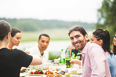 Portrait of smiling young man enjoying dinner with friends at table in backyard - p426m2035684 by Maskot