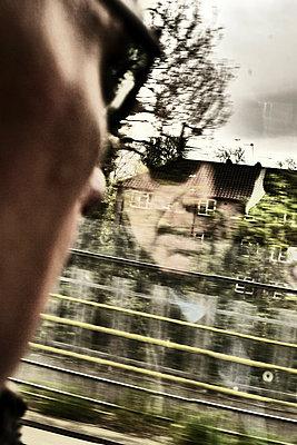 Man looking through train window - p597m1161403 by Tim Robinson