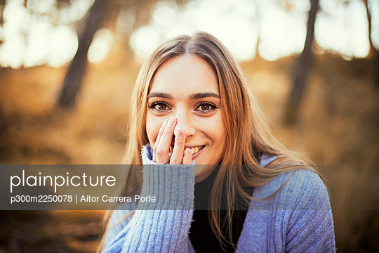 Beautiful smiling woman in woolen sweater at park during winter - p300m2250078 by Aitor Carrera Porté