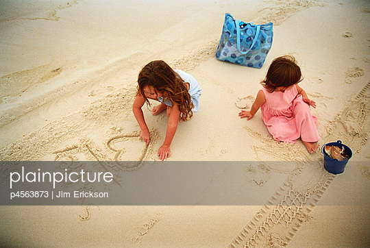 Two little girls writing and drawing in wet sand. - p4563873 by Jim Erickson