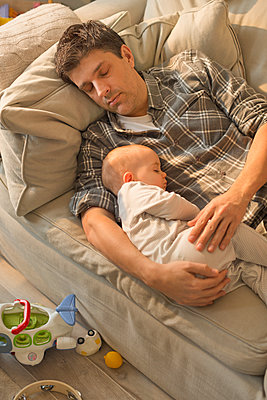 Exhausted father and baby son sleeping on sofa - p1023m1446507 by Tom Merton