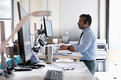 Businessman with headset using computers at sit-stand desk in office - p1192m2062432 by Hero Images