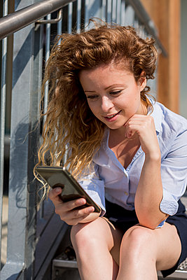 Businesswoman sitting on stairs using cell phone - p300m1166517 by Mauro Grigollo