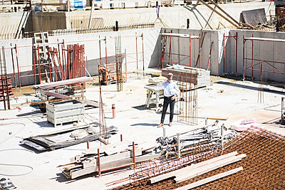 Man on cell phone on construction site - p300m2005463 by Robijn Page
