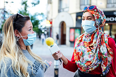 Female journalist interviewing woman with microphone in city during COVID-19 - p300m2240885 by Jose Luis CARRASCOSA
