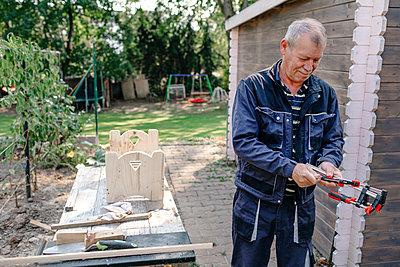 Senior man doing carpentry work in backyard - p300m2276985 by Oxana Guryanova