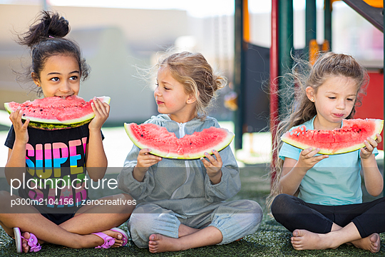 Three girls eating watermelons in kindergarten - p300m2104156 by zerocreatives