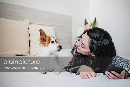 Woman looking at Jack Russell Terrier while lying on bed at home - p300m2264978 by Eva Blanco