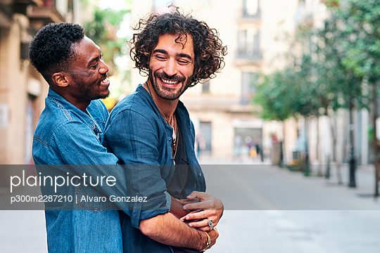 Happy gay man embracing male friend from behind on road - p300m2287210 by Alvaro Gonzalez