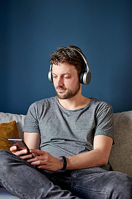 Young man with headphones and smartphone - p1124m1589441 by Willing-Holtz
