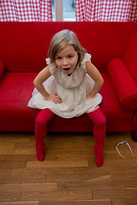 Mädchen auf rotem Sofa - p1212m1091997 von harry + lidy