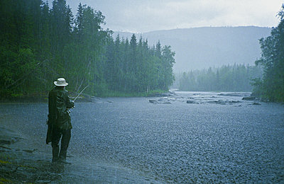 Man fishing in heavy rain - p1418m1571758 by Jan Håkan Dahlström