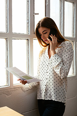 Young woman on cell phone looking at document at the window - p300m2079192 by Bonninstudio