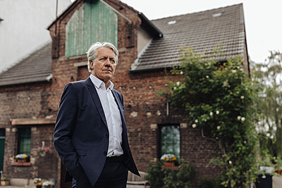 Portrait of a senior businessman in front of a farmhouse - p300m2202692 by Gustafsson