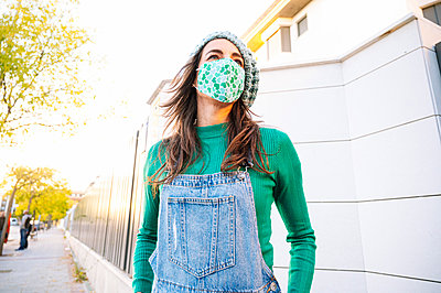 Mature woman looking away while wearing protective face mask standing on street during sunny day - p300m2225897 by Jose Luis CARRASCOSA