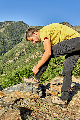 Man tying sports shoe while standing in forest on sunny day - p300m2227265 by Veam