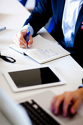 Close-up mid section of businessman writing notes at table - p426m811607f by Astrakan