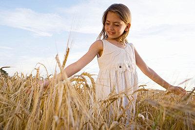 Young girl walking in corn field - p4292223f by Adie Bush
