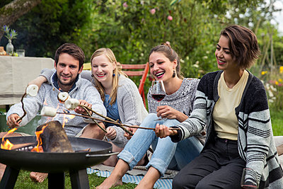 Friends roasting marshmallows - p788m1165411 by Lisa Krechting