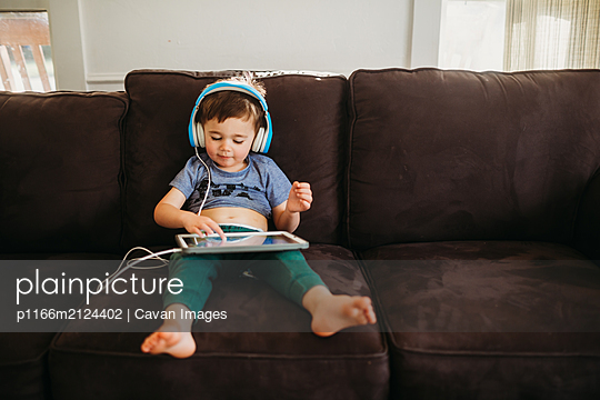 Young boy happily using tablet to play educational games at home - p1166m2124402 by Cavan Images