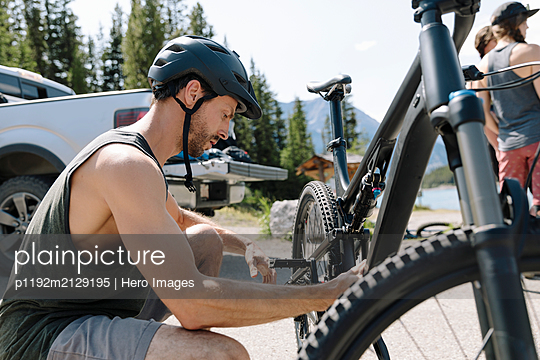 Man adjusting mountain bike in sunny parking lot - p1192m2129195 by Hero Images