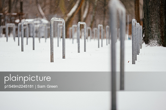 Deserted bicycle stands in the snow - p1549m2245181 by Sam Green