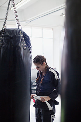 Young woman tying judo belt next to punching bag in gym - p1023m1506455 by Sam Edwards