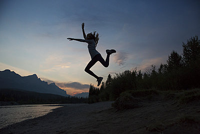 Silhouette happy teenage girl jumping at lakeshore against sky at Banff National Park during sunset - p1166m2025243 by Cavan Social