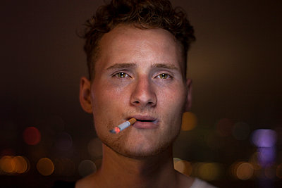 Young man smoking a cigarette - p1324m1165182 by Michael Hopf